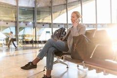 Voyageur féminin parlant à son téléphone portable tout en attendant pour monter à bord d'un avion aux portes de départ sur le ter image stock