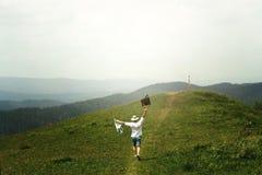 Voyageur heureux d'homme tenant la carte et le fonctionnement jusqu'au dessus de la colline ensoleillée Photographie stock libre de droits