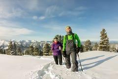 Voyageur heureux de deux femmes avec des sacs à dos marchant dans la forêt de montagnes d'hiver Images stock