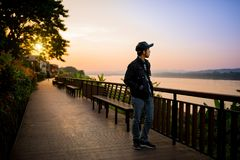 Voyageur marchant au-dessus du pont en bois près de la rivière Image stock
