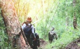 Voyageur marchant dans le groupe en bambou de montagne de forêt/randonneurs d'hommes d'amis marchant avec les sacs à dos et l'équ image libre de droits