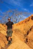 Voyageur masculin caucasien blanc dans les vêtements de sport : bottes, shorts, positions de port en verre contre les roches jaun image libre de droits