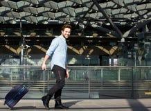 Voyageur masculin de sourire marchant avec la valise Image stock