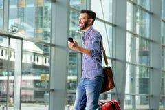 Voyageur masculin de sourire marchant avec le sac et le téléphone portable Images libres de droits