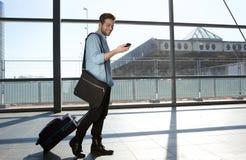 Voyageur masculin heureux marchant avec les sacs et le téléphone portable Images stock