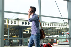 Voyageur masculin marchant avec le sac et parlant au téléphone portable Photo libre de droits