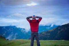 Voyageur observant le mouvement des nuages lourds au-dessus de la montagne Photos libres de droits