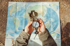 Voyageur recherchant la direction avec une boussole sur le fond de la carte Photographie stock libre de droits