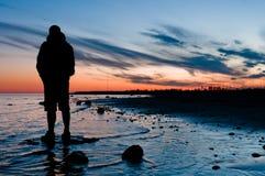 Voyageur regardant sur le coucher du soleil Photographie stock