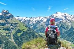 Voyageur s'asseyant sur une falaise avec un sac à dos admirant le mountai photo libre de droits