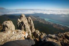 Voyageur s'asseyant sur une falaise de sommet de montagne rocheuse au-dessus des nuages Photo de point de vue des jambes en augme Photos stock