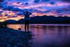 Voyageur se tenant sur le rivage avec le ciel coloré de coucher du soleil images stock