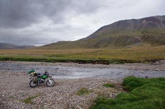 Voyageur simple de moto avec des valises se tenant sur la banque en pierre du courant de rivière de montagne Photographie stock