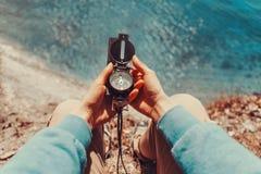 Voyageur tenant une boussole sur le littoral Photo stock