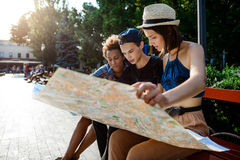 Voyageurs d'amis souriant, regardant l'itinéraire la carte, se reposant sur le banc Photographie stock libre de droits