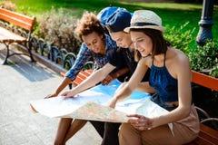 Voyageurs d'amis souriant, regardant l'itinéraire la carte, se reposant sur le banc Photo libre de droits
