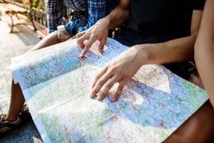 Voyageurs d'amis souriant, regardant l'itinéraire la carte, se reposant sur le banc Images libres de droits
