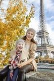 Voyageurs de mère et d'enfant s'asseyant sur le parapet à Paris Photographie stock libre de droits