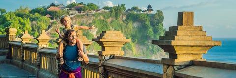Voyageurs de papa et de fils dans le temple de Pura Luhur Uluwatu, Bali, Indonésie Paysage étonnant - falaise avec le ciel bleu e photos stock