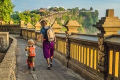 Voyageurs de papa et de fils dans le temple de Pura Luhur Uluwatu, Bali, Indonésie Paysage étonnant - falaise avec le ciel bleu e image libre de droits