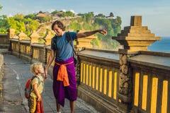 Voyageurs de papa et de fils dans le temple de Pura Luhur Uluwatu, Bali, Indonésie Paysage étonnant - falaise avec le ciel bleu e photo stock