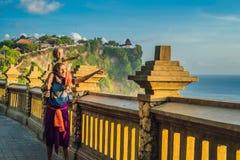 Voyageurs de papa et de fils dans le temple de Pura Luhur Uluwatu, Bali, Indonésie Paysage étonnant - falaise avec le ciel bleu e photographie stock