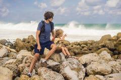 Voyageurs de papa et de fils sur stupéfier la plage de Melasti avec de l'eau turquoise, île Indonésie de Bali Déplacement avec le image stock