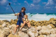 Voyageurs de papa et de fils sur stupéfier la plage de Melasti avec de l'eau turquoise, île Indonésie de Bali Déplacement avec le photographie stock