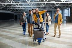 Voyageurs de réjouissance avec l'embarquement allant de chariot à bagage Image libre de droits