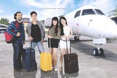 Voyageurs divers avec des valises près d'un avion Photo libre de droits