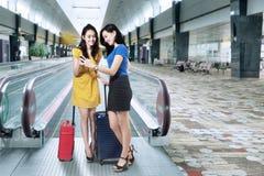 Voyageurs féminins avec le téléphone portable dans l'aéroport Photos stock
