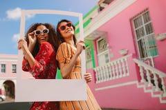 Voyageurs féminins avec un cadre de tableau dehors image libre de droits