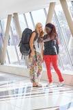2 voyageurs féminins dans le couloir d'aéroport prenant des selfies Photographie stock
