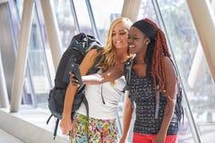 2 voyageurs féminins dans le couloir d'aéroport prenant des selfies Images libres de droits