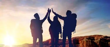 Voyageurs faisant haut cinq au-dessus du lever de soleil photo libre de droits