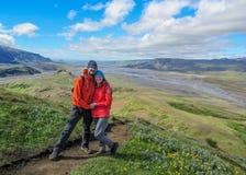 Voyageurs heureux homme et femme d'aventure de couples dans des imperméables avec la cascade à l'arrière-plan, à la liberté et au image stock