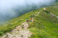 Voyageurs - hommes et garçon avec la hausse de sacs à dos le long de l'arête Photographie stock libre de droits