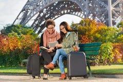 Voyageurs s'asseyant sur un banc près de Tour Eiffel Photographie stock