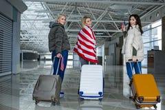 Voyageurs satisfaisants avec des cas se déplaçant vers la sortie terminale Images stock