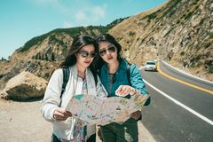 Voyageurs trouvant quelque chose sur la carte de guide image libre de droits