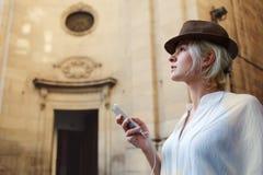 Voyageuse attirante de femme dans le chapeau à la mode attendant le faire appel à son téléphone de cellules pendant le temps de r Photos stock