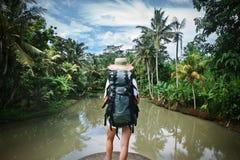 Voyageuse de femme avec le sac à dos et le chapeau se tenant près de la rivière tropicale Images libres de droits