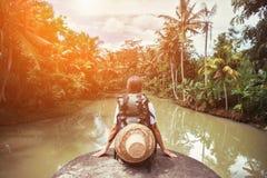 Voyageuse de femme avec le sac à dos se reposant près de la rivière tropicale Photos stock