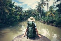 Voyageuse de femme avec le sac à dos se reposant sur le bord et regardant la rivière tropicale Photo stock