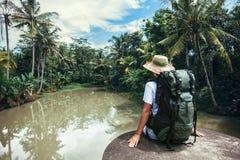 Voyageuse de femme avec le sac à dos se reposant sur le bord près de la rivière tropicale Photo libre de droits