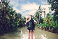 Voyageuse de femme avec le sac à dos se tenant près de la rivière tropicale Photographie stock libre de droits