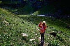 Voyageuse de femme avec le sac à dos sur le beau paysage de vallée de montagne Photos stock