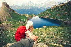 Voyageuse de femme avec le sac à dos tenant la hausse suivante de voyage de main d'homme Image stock
