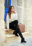 Voyageuse de femme avec se reposer de valise rêveur à sa maison Images stock