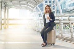 Voyageuse de femme d'affaires avec le bagage au fond de ville Photographie stock libre de droits